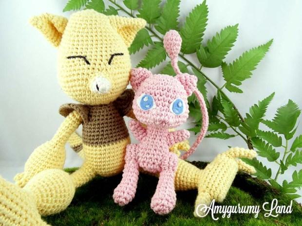 Amigurumis en crochet des pokémons Abra et Mew. Abra est assis et tiens Mew dans ses bras. Ils sont placé sur un morceau de mousse avec une branche de fougère en fond.